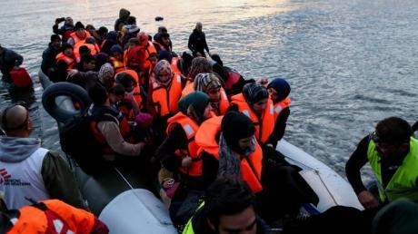 Freiwillige helfen auf der griechischen Insel Lesbos völlig erschöpften Flüchtlinge aus ihrem Boot. Foto: Kay Nietfeld/dpa
