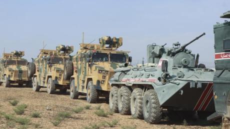 Türkische und russische Soldaten in Panzer und Militärfahrzeugen patroullieren an der türkisch-syrischen Grenze. Foto: Uncredited/AP/dpa