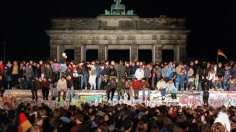 Jubelnde Menschen sitzen nach der Maueröffnung auf den Grenzanlagen am Brandenburger Tor. Foto: Wolfgang Kumm/dpa