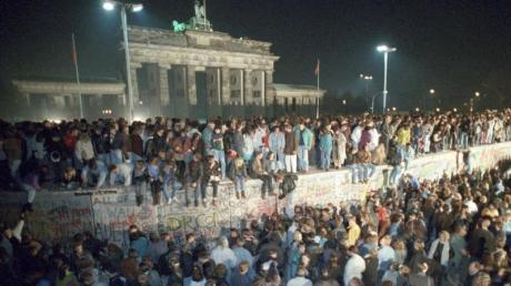 Menschen feiern auf der Berliner Mauer in der Nacht vom 9. auf den 10. November 1989.