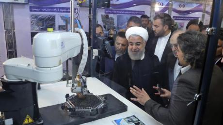 Irans Präsident Hassan Ruhani (M.) lässt sich neue Entwicklungen in der Atomenergie im Rahmen des «Nationalen Atomtags» erklären. Foto: Uncredited/Iranian Presidency Office/AP/dpa