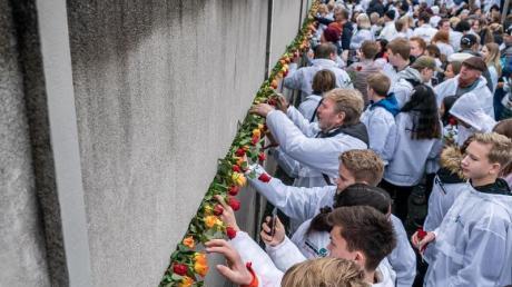Besucher stecken Blumen bei der Gedenkveranstaltung der Stiftung Berliner Mauer an der Bernauer Straße in Mauerschlitze der Hinterlandmauer. Foto: Michael Kappeler/dpa