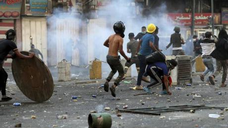 Demonstranten stehen in einer Wolke aus Tränengas. Foto: Hadi Mizban/AP Photo/dpa