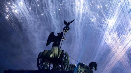"""Ein Feuerwerk wird bei der Feier anlässlich der Festivalwoche """"30 Jahre Friedliche Revolution – Mauerfall"""" am Brandenburger Tor zum Abschluss gezeigt. Foto: Bernd von Jutrczenka/dpa"""