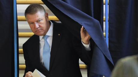 Klaus Iohannis, Präsident von Rumänien, verlässt eine Wahlkabine mit einem Stimmzettel. Foto: Vadim Ghirda/AP/dpa