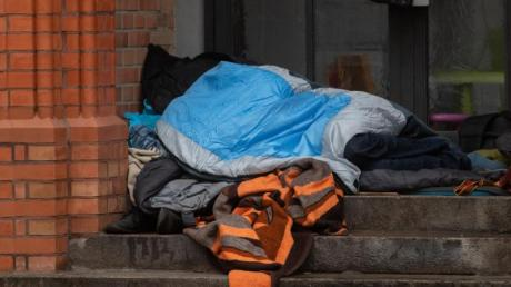 Ein Obdachloser liegt in einem Eingang einer Kirche in Berlin. Obdachlos sind den Zahlen der Wohungslosenhilfe zufolge etwa 41.000 Menschen inDeutschland. Foto: Paul Zinken/dpa