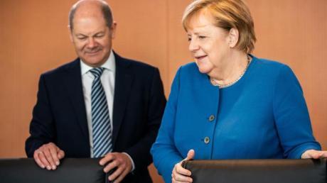 Bundesfinanzminister Scholz und Bundeskanzlerin Merkel vor Beginn einer der wöchentlichen Sitzungen des Bundeskabinetts. Foto: Michael Kappeler/dpa