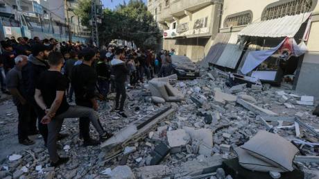 Anwohner und Passanten stehen nach dem israelischen Luftangriff vor dem beschädigte Haus von Baha Abu Al Ata.