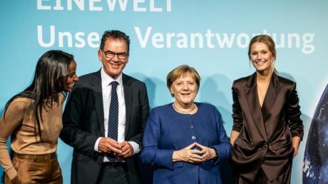 Bundeskanzlerin Angela Merkel und Entwicklungsminister Gerd Müller stehen zusammen mit den Ministeriums-Botschafterinnen Sara Nuru (l) und Toni Garrn (r) bei der Veranstaltung «Eine Welt - Unsere Verantwortung». Foto: Michael Kappeler/dpa