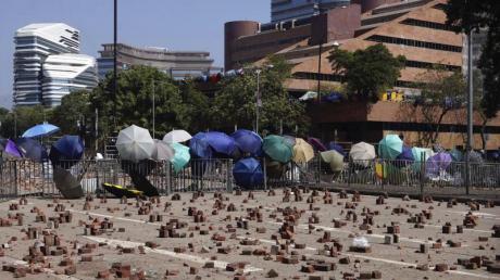 Auf einer Straße vor einer Barrikade, die von Demonstranten der Polytechnischen Universität Hongkong gebaut wurde, sind Ziegelsteine verstreut. Foto: Vincent Yu/AP/dpa