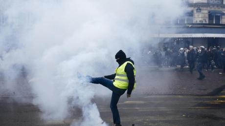 Ein Demonstrant tritt einen Tränengasbehälter von sich weg. Foto: Kamil Zihnioglu/AP/dpa