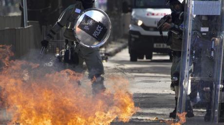 Ein Molotow-Cocktail geht vor Polizisten in Flammen auf. Foto: Ng Han Guan/AP/dpa
