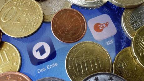 Euromünzen liegen neben den Logos der Apps von ARD und ZDF. Foto: Soeren Stache/dpa