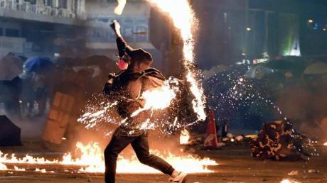 Ein Demonstrant wirft einen Molotowcocktail auf die Polizei. Foto: -/kyodo/dpa