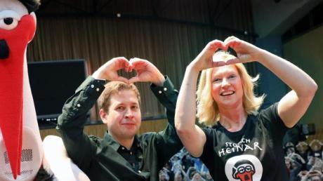 Kevin Kühnert und Manuela Schwesig bilden das Symbol «Herz statt Hetze» zur Unterstützung der Proteste gegen ein Treffen des rechten Flügels der AfD in Binz, daneben Storch Heinar, eine Parodiefigur auf die Neonazi-Modemarke Thor Steinar.
