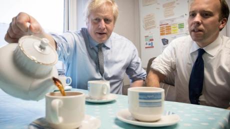Premierminister Boris Johnson und Gesundheitsminister Matt Hancock widmen sich beim Besuch eines Krankenhauses einer britischen Tradition - dem Teetrinken.