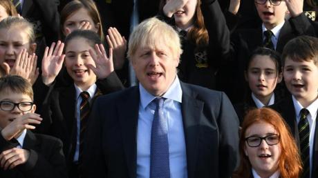 Großbritanniens Premierminister Boris Johnson (M) steht zwischen Schüler bei seinem Besuch eines Colleges.