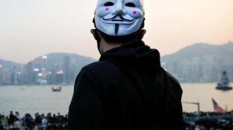 Ein prodemokratischer Demonstrant mit Guy-Fawkes-Maske beobachtet eine Kundgebung in Hongkong.