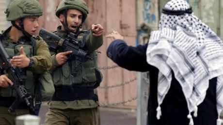 Ein Mann streitet in Hebron im Westjordanland mit israelischen Soldaten.