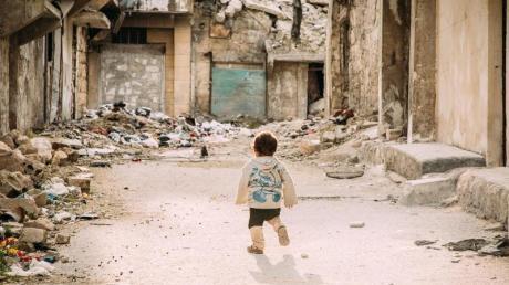 Ein kleiner Junge geht durch eine vom Bürgerkrieg zerstörte Straße in der syrischen Metropole Aleppo.