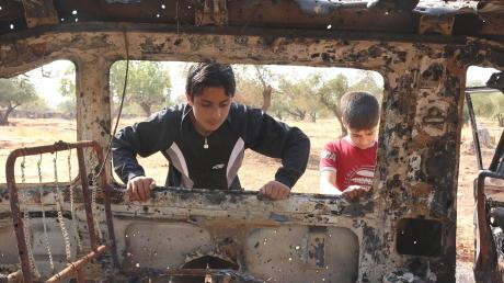 Kinder spielen nahe der Stadt Idlib an einem zerstörten Auto. Noch immer findet der Krieg in Syrien kein Ende.
