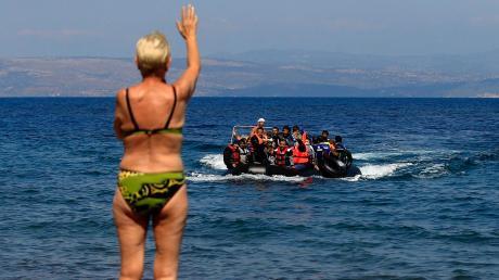 Ein Badegast winkt Flüchtlingen aus Syrien zu, die aus der Türkei mit einem Schlauchboot an die Küste der griechischenInsel Lesbos kommen. In Deutschland beherrschte das Thema Migration ab 2015 die Schlagzeilen.