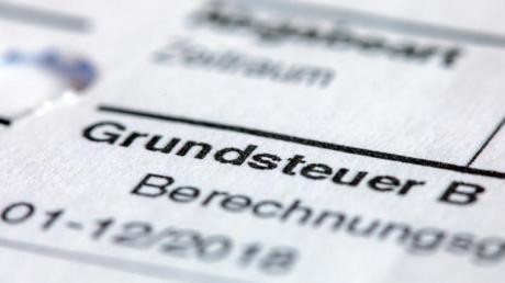 Ein Abgabenbescheid für die Entrichtung der Grundsteuer liegt auf einem Schreibtisch.