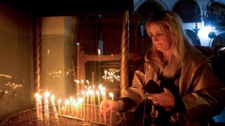 Weihnachten in Bethlehem:Eine Besucherin zündet eine Kerze in der Geburtskirche an.