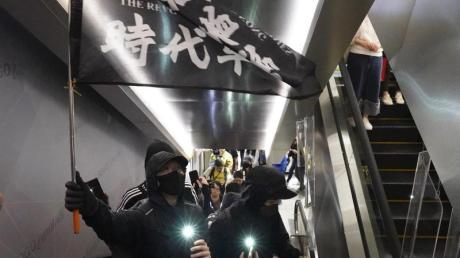 Demonstranten mit Mundschutz tragen eine Flagge mit der Aufschrift «Befreit Hongkong, die Revolution unserer Zeit» in einem Einkaufszentrum.