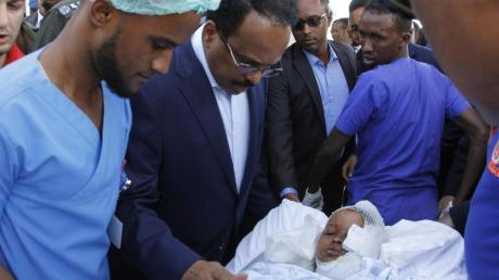 Somalias Präsident Mohamed Abdullahi Mohamed (Mitte l) besucht Opfer, die bei der Explosion einer Autobombe am 28.12.2019 verletzt wurden.