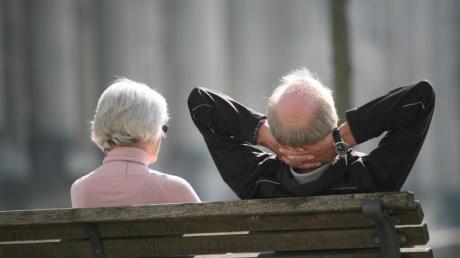 Ein Rentnerpaar sitzt auf einer Bank und sonnt sich.