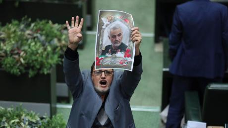Ein Abgeordneter hält im iranischen Parlament das Konterfei des getöteten Generals Soleimani in die Höhe. Die Rufe nach Rache ebben nicht ab.
