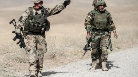 Bundeswehrsoldaten und kurdische Peshmerga Soldaten gehen in der Ausbildungseinrichtung Bnaslawa bei einer Übung am Rand einer Straße entlang. Nun prüft die Bundesregierung den Teilrückzug der Soldaten aus Erbil.