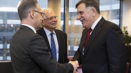 Außenminister Heiko Maas und Libyens international anerkannter Regierungschef Fajis al-Sarradsch begrüßen sich in Brüssel.