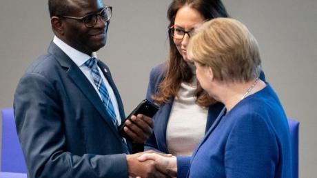 Bundeskanzlerin Angela Merkel (CDU) stellt sich hinter den SPD-Bundestagsabgeordneten Karamba Diaby (li), nachdem dessen Bürgerbüro angegriffen wurde.