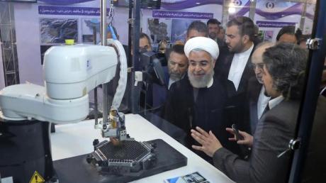 Der iranische Präsident Hassan Ruhani (M.) lässt sich neue Entwicklungen in der Atomenergie im Rahmen des «Nationalen Atomtags» erklären.
