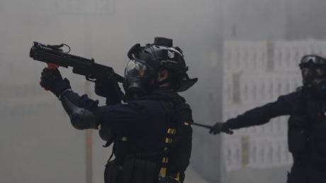 Ein Polizist zielt mit Tränengas auf Demonstranten bei regierungskritischen Protesten.