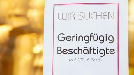 Geringfügig Beschäftigte gesucht: Eine Stellenanzeige für einen Minijob auf 400 Euro Basis klebt im Schaufenster eines Textilgeschäfts.