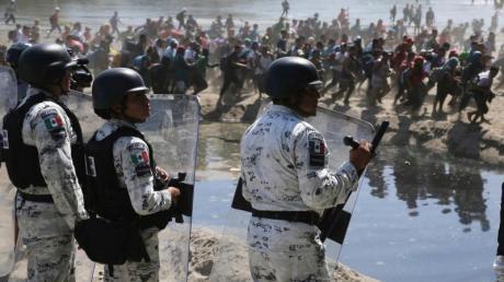 Migranten passieren mexikanischen Nationalgardisten am Grenzfluss Río Suchiate zwischen zwischen Guatemala und Mexiko.