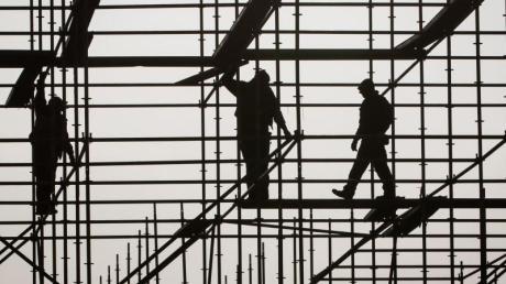 Gerüstbauer errichten in Hamburg auf einer Brückenbaustelle in der Hafencity ein Gerüst.