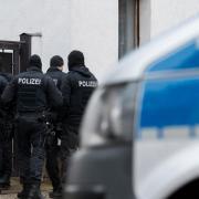 """Polizisten und ein Polizeiwagen stehen vor einem Wohnhaus im Ortsteil Vieselbach. Bundesinnenminister Seehofer (CSU)hat die rechtsextreme Gruppe """"Combat 18"""" verboten."""