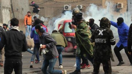 Rauch und Tränengas steigen bei Zusammenstößen zwischen Demonstranten und Sicherheitskräften in Bagdad auf.
