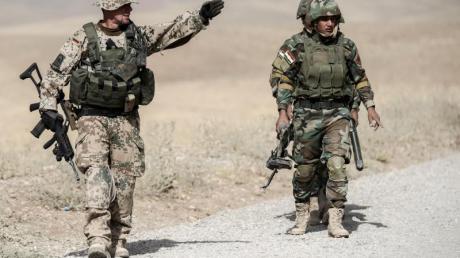 Ein Bundeswehrsoldat und Kämpfer der kurdischen Peshmerga während der Ausbildung nahe Erbil im Norden des Irak.