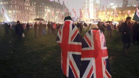 Brexit-Anhänger laufen mit der britischenNationalflagge über den Parliament Square in London.