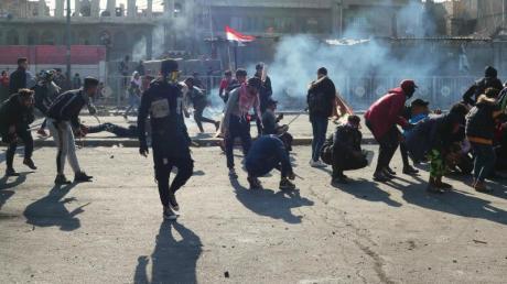 Demonstranten in Bagdad gehen vor Tränengasgeschossen in Deckung.