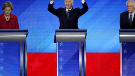 Gestikulierend: Elizabeth Warren (l) und Bernie Sanders (r) hören Joe Biden während der Debatte zu.