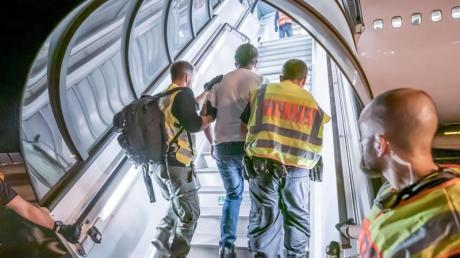 Abschiebung:Polizeibeamte begleiten einen Afghanen auf dem Flughafen Leipzig-Halle in ein Charterflugzeug.