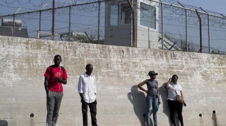 Migranten an einer Mauer des Flüchtlingslagers Moria auf der Insel Lesbos.
