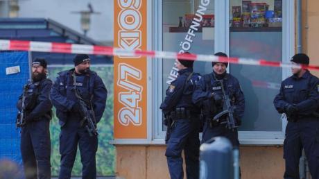 Mit Maschinenpistolen bewaffnete Einsatzkräfte der Polizei vor einem Kiosk am Tatort in Hanau-Kesselstadt.