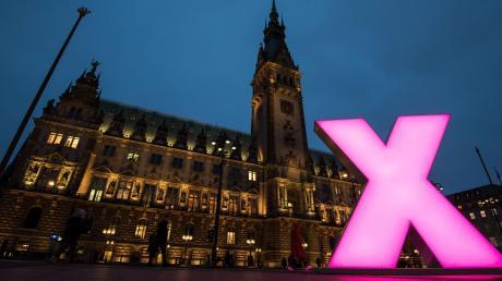 Ein beleuchtetes Kreuz steht als symbolisches Wahlkreuz vor dem Hamburger Rathaus.
